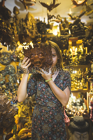young woman holding barong mask in