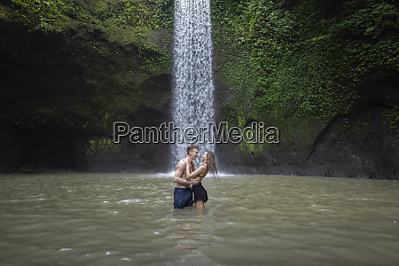 young couple embracing in river by
