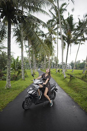 young woman on motorcycle by palm