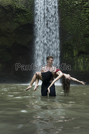 young man carrying young woman in