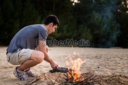 mann bereitet lagerfeuer vor