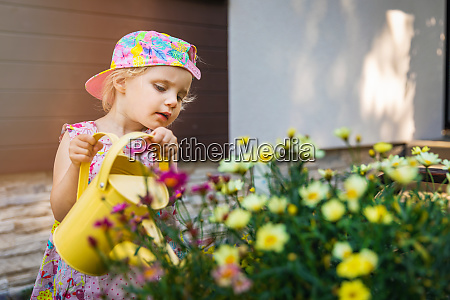 little girl watering flowers with yellow