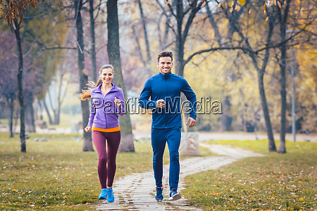 woman and man running in autumn