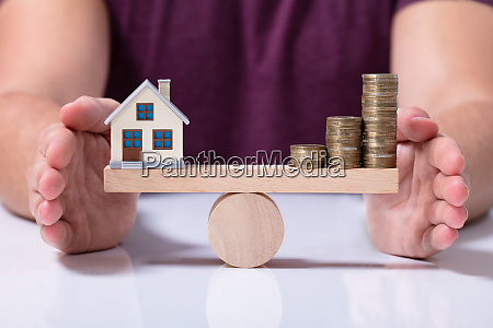 house model and money coins balancing