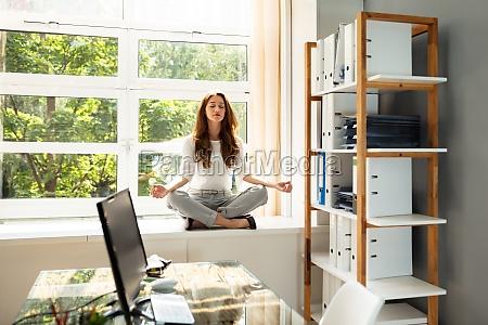 geschaeftsfrau meditieren in lotus position
