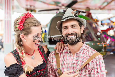 couple visiting carrousel at the oktoberfest