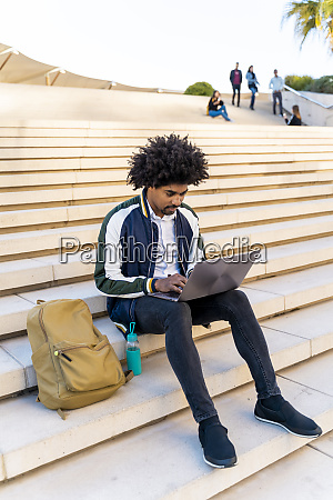 casual businessman sitting on stairs working
