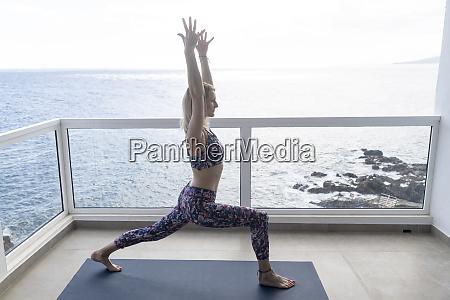 woman practicing yoga on balcony position