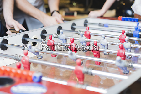 close up of colleagues playing foosball