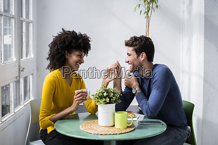 happy affectionate couple sitting at table