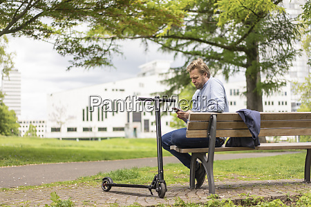 businessman with e scooter sitting on
