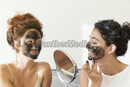 two happy young women applying facial