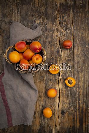 aprikosen im korb auf dunklem holz