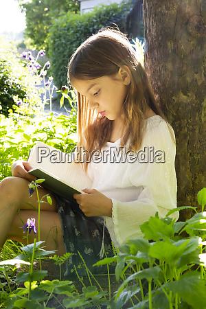 little girl leaning against tree trunk