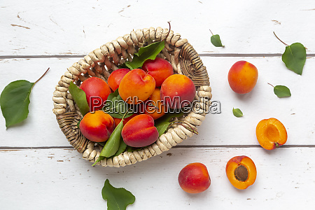 aprikosen im korb auf weissem holz