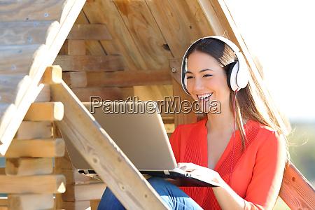 glueckliche frau mit laptop und kopfhoerer