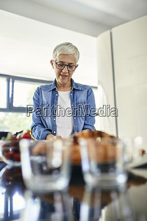 senior woman standing in kitchen chopping