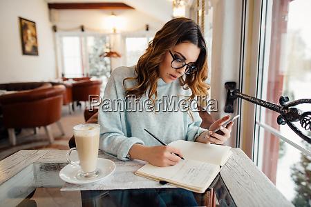 junge geschaeftsfrau im cafe schreibt notizen