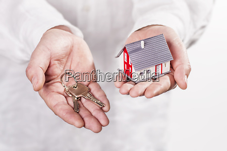 hands holding house and keys