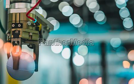 closeup roboter handmaschine nimmt weisse kugel