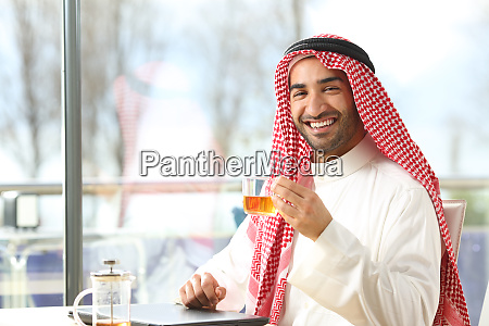 happy arab man holding a cup