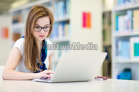 huebsche studentische studentin in einer bibliothek