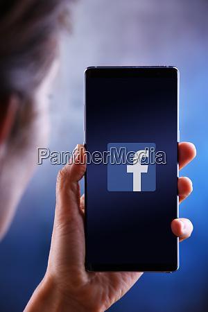 frau haelt smartphone mit logo von