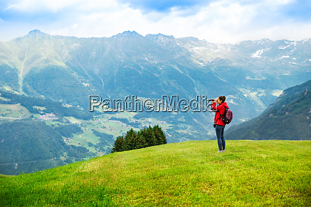 woman in mountains looking in spyglass