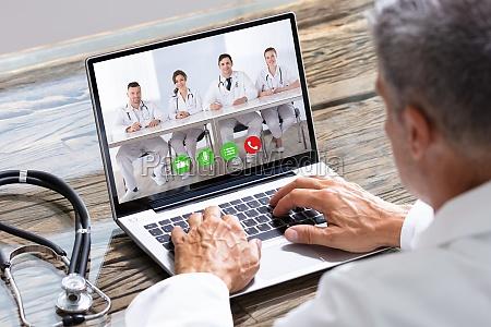 arzt mit videokonferenz auf laptop