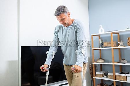 behinderter mann mit kruecken zu gehen