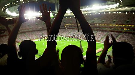 fussballstadion voller fans jubelt nach tor