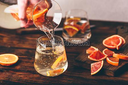giessen von infundiertem wasser mit orangen