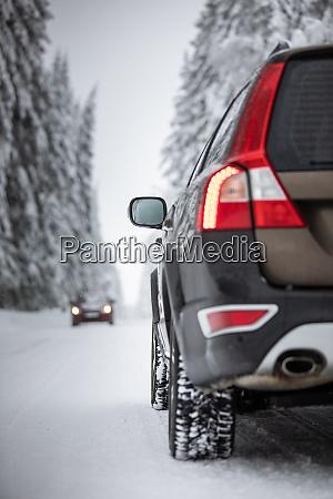 auto auf verschneiter winterstrasse inmitten von