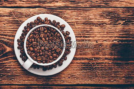 weisse tasse voller geroesteter kaffeebohnen