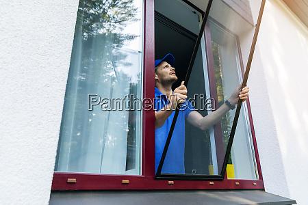 man installing mosquito net wire mesh