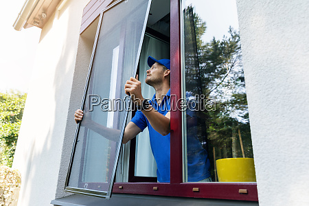 man installing insect mesh screen on