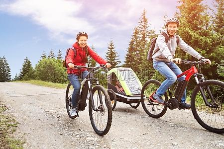 familie mit kind in anhaenger reiten