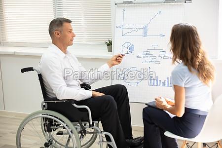 behinderter geschaeftsmann bei der praesentation seines