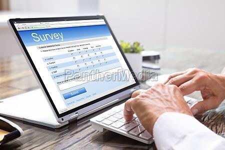 mann gibt online umfrage auf laptop