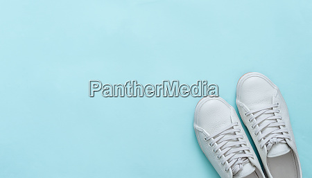 white sneakers on blue copy space