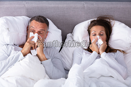 mature couple blowing their nose