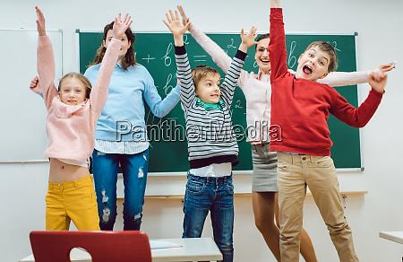 lehrer und schueler der grundschule springen