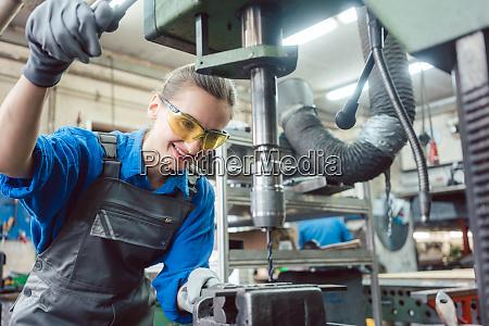 woman worker in metal workshop using