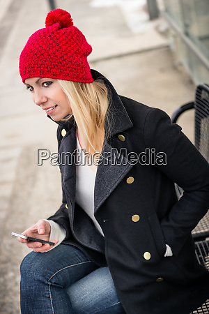 woman using phone while waiting for