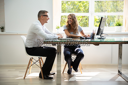 happy businesspeople working in office using