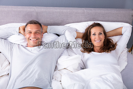 smiling couple lying on bed