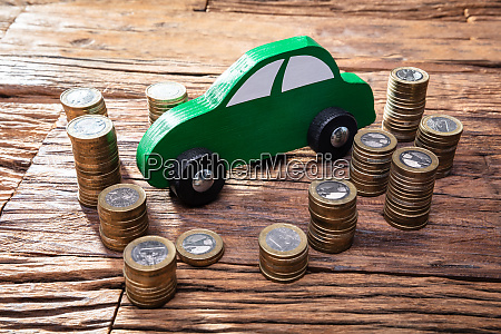 stack of coins with green car