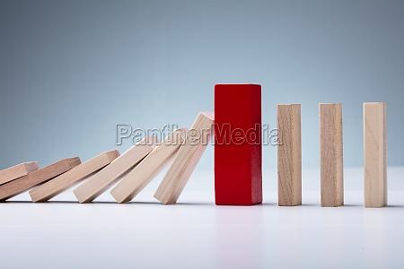 roter holzblock inmitten fallender und aufrechter