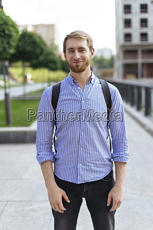 mann traegt gestreiftes hemd und rucksack