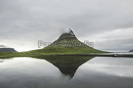 kirkjufell unter bewoelktem himmel in island